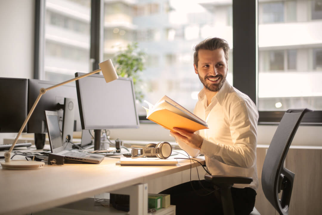 a man sits at a desk with a computer - register-your-business