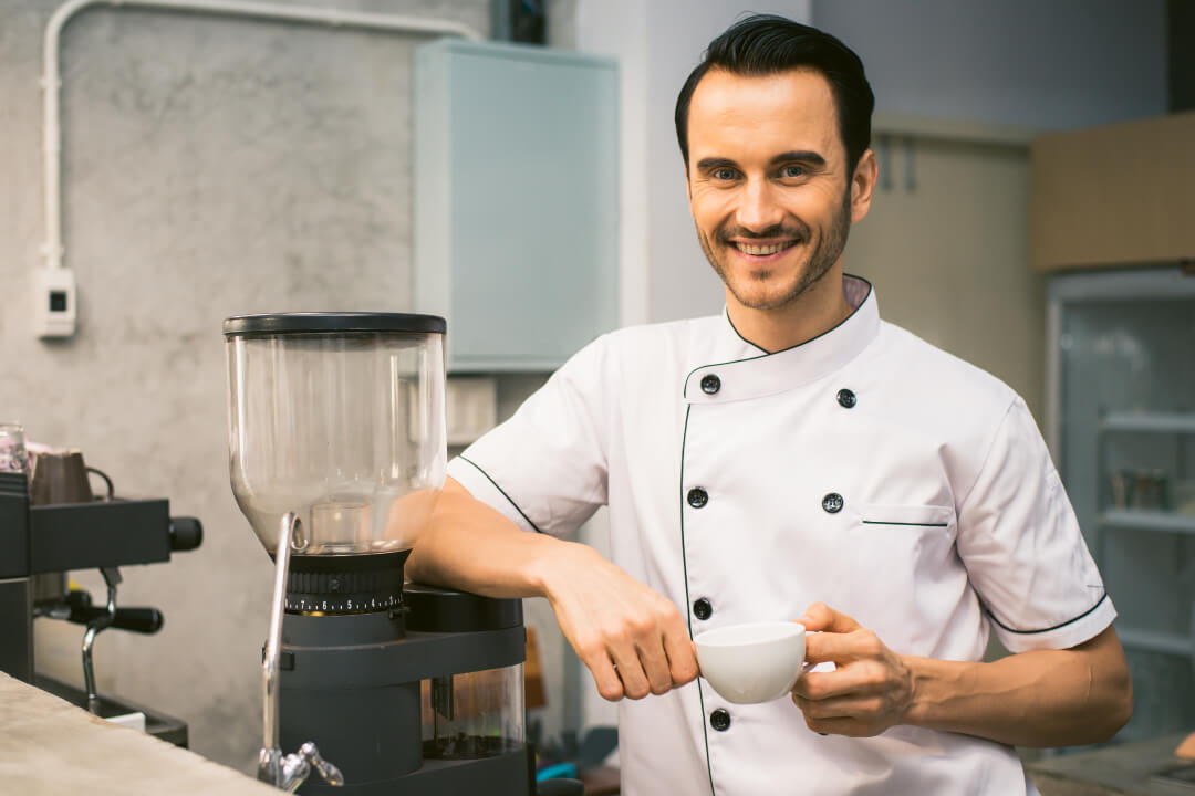 a man in a cook's clothing poses and smiles - register-your-business