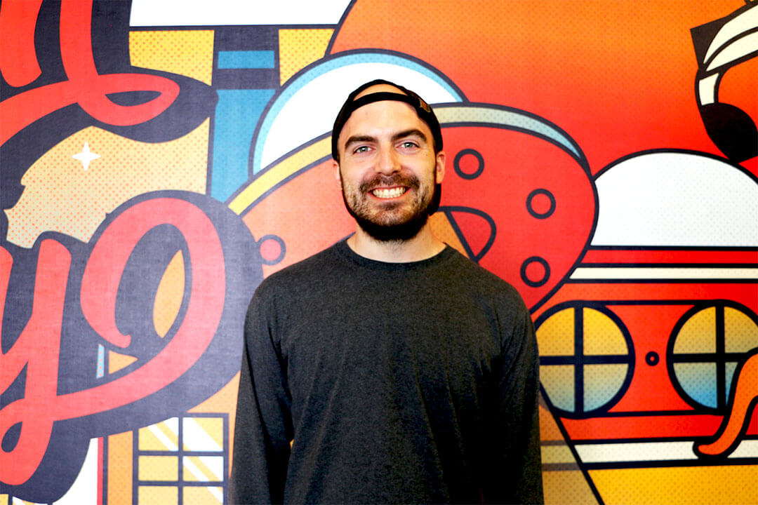 An image of Missouri entrepreneur Seth Kitchen in front of the mural wall at efactory in Sprigfield Missouri.