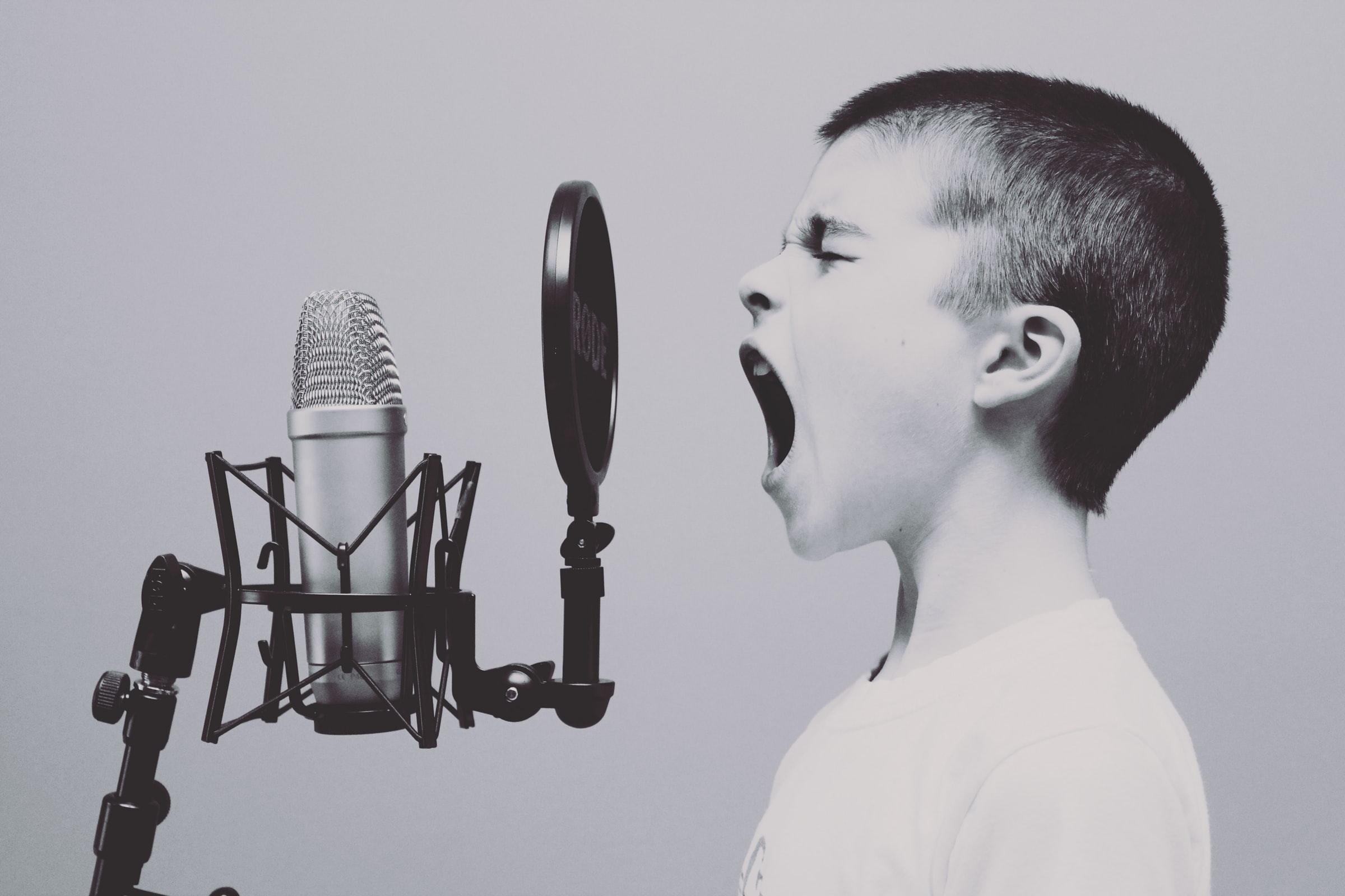 A boy sings into a microphone