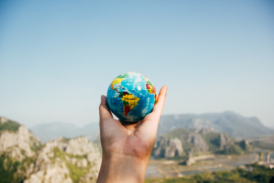 a person holds a miniature globe in front of a landscape - Global Market Access Program Increase International Sales
