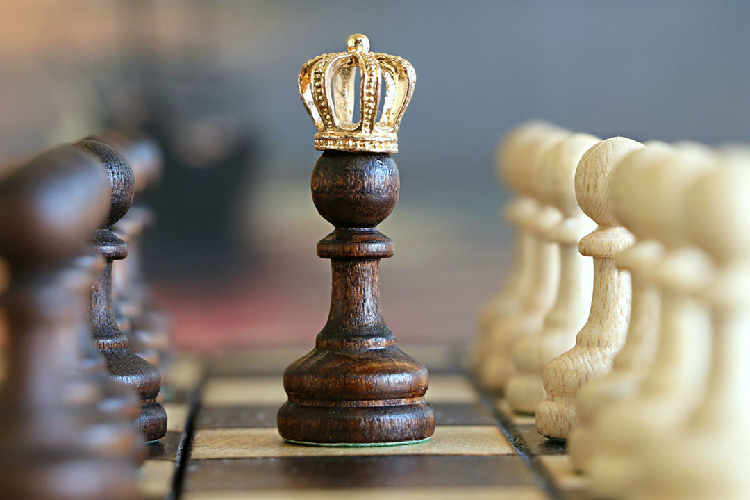 A chess piece with a crown is surrounded by pawns