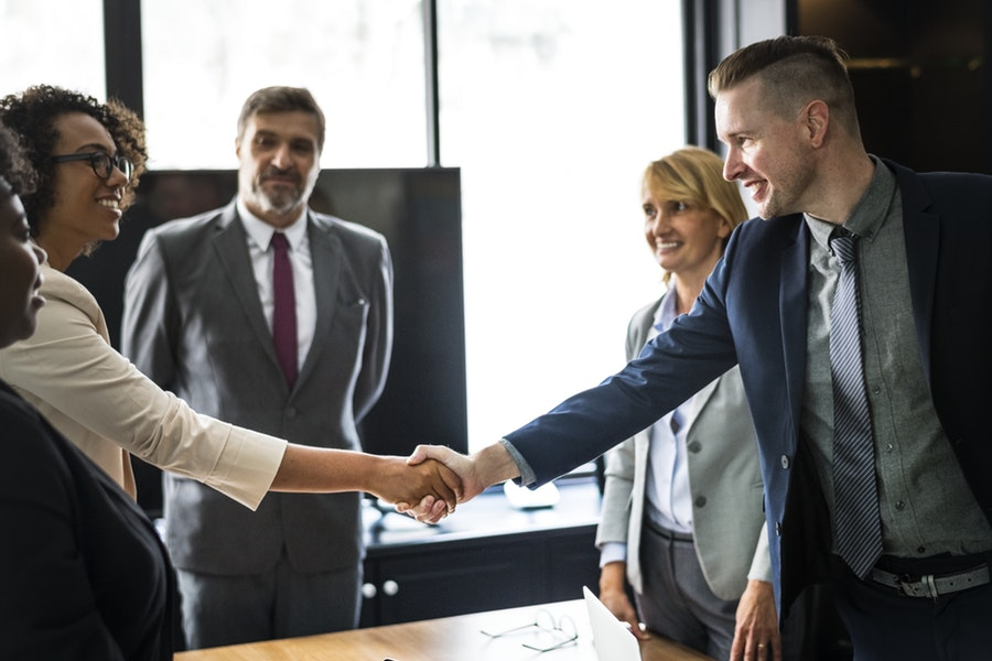 man in a business suit shakes hand - hiring-employees-in-missouri-read-this first