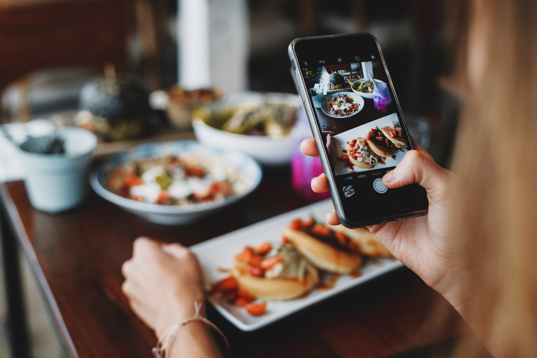 A woman uses a smartphone to take a picture of food on a table