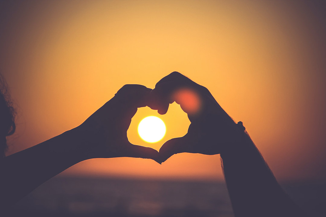 Hands make a heart shape with the sun in the middle