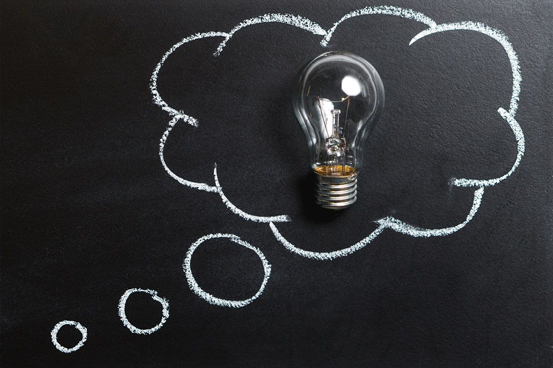 A light bulb surrounded by a thought bubble on a chalkboard