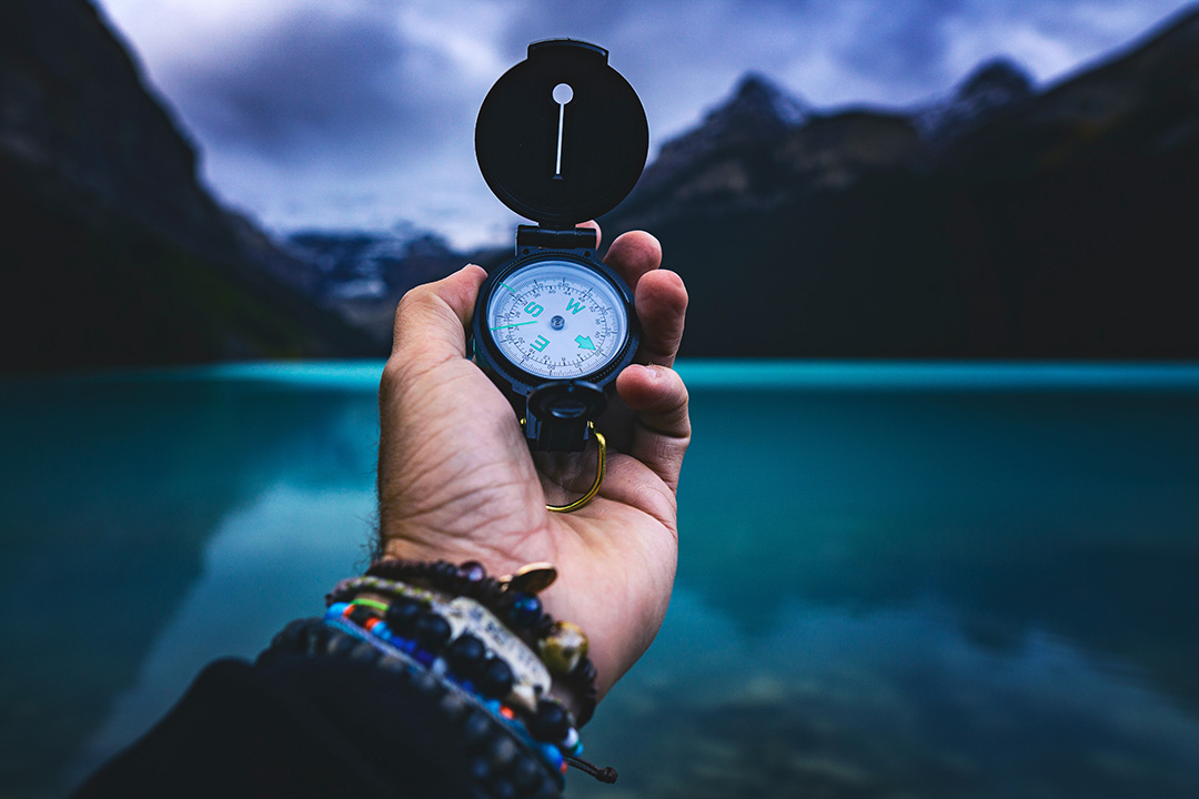 A person holds a compass near an outdoor scene